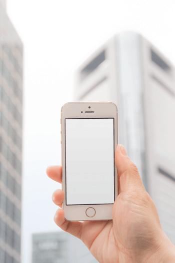 手拿白色苹果手机拍照实物图